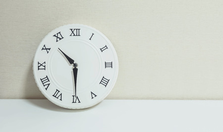 69168943 - closeup white clock for decorate show half past ten or 10:30 a.m. on white wood desk and cream wallpaper textured background with copy space